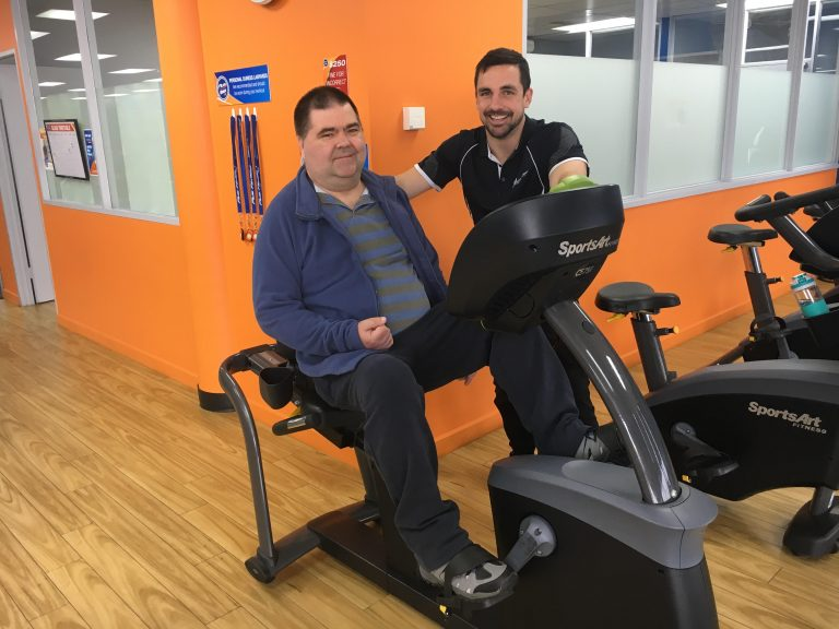 Client enjoying a recumbent bike after stroke